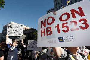 Protesters call for Mississippi Gov. Phil Bryant to veto House Bill 1523, which they say allow discrimination against LGBT people, during a rally outside the Governor's Mansion in Jackson, Miss., Monday, April 4, 2016. (AP Photo/Rogelio V. Solis)